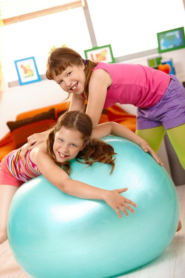 Petites filles jouant avec la bille d'exercice photographie stock