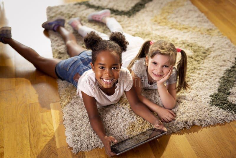 Petites filles jouant des jeux vidéo sur une tablette photos libres de droits