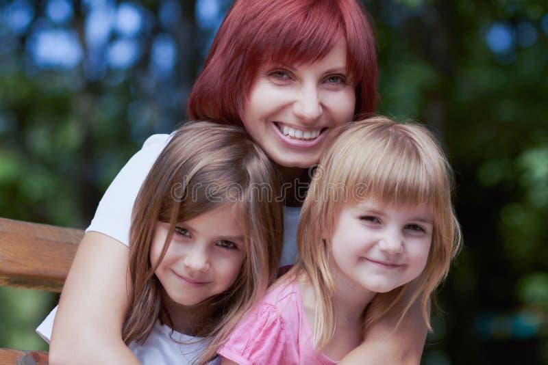 Petites filles mignonnes avec leur maman dehors image libre de droits