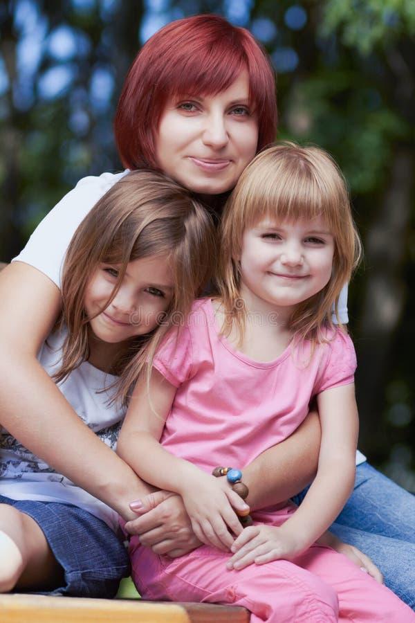 Petites filles mignonnes avec leur maman dehors images stock