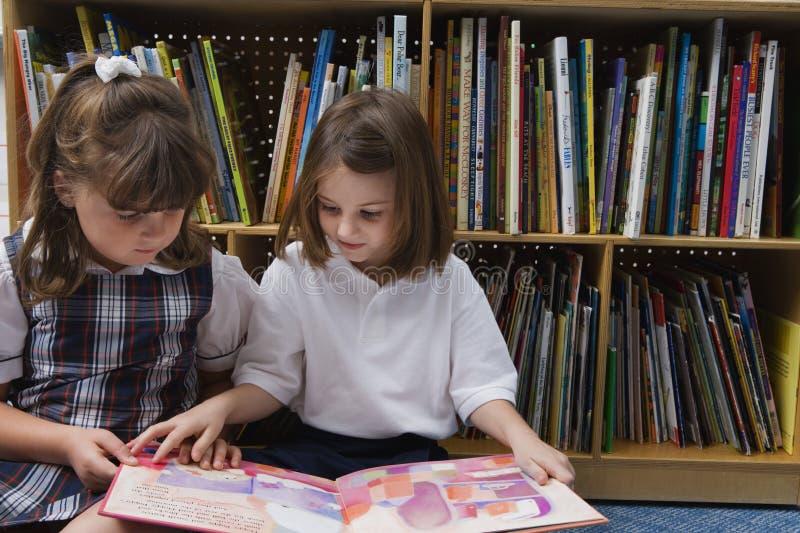 Petites filles regardant un livre d'images photo stock