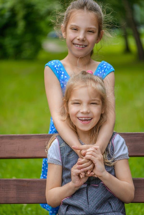 Petites filles s'asseyant sur le banc photo libre de droits