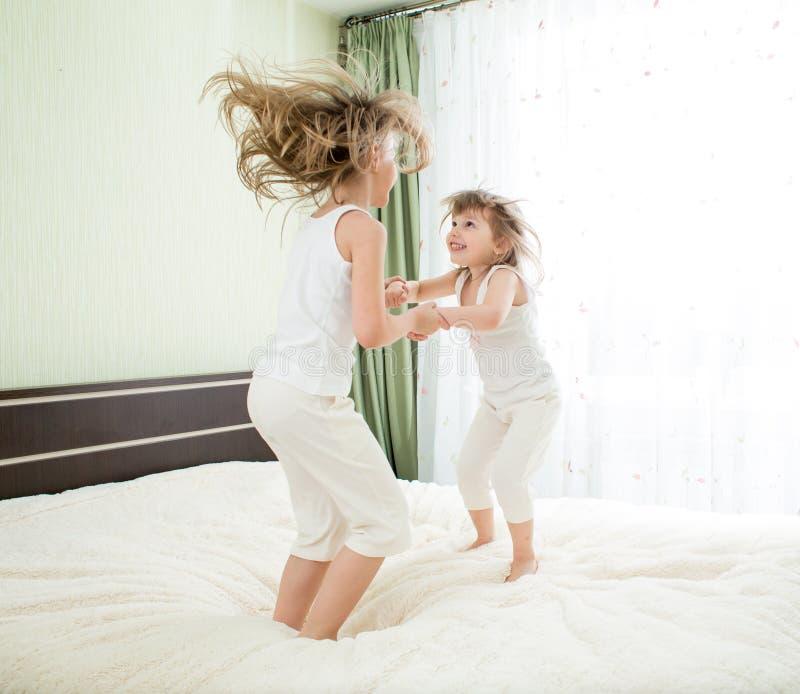 Petites filles sautant sur le lit ensemble photographie stock