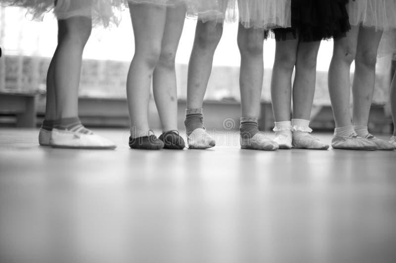 Petites jambes de ballerines se tenant dans une rangée photo stock