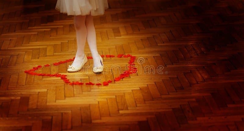 Petites jambes de fille de demoiselle d'honneur dans la robe blanche sur le dancefloor de mariage avec des pétales de rose photos stock