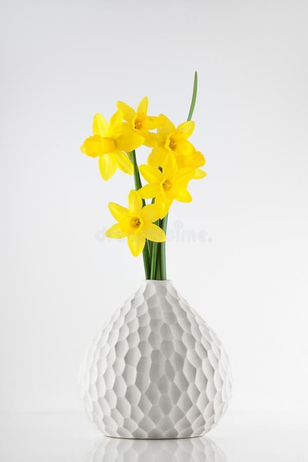 Petites jonquilles jaunes lumineuses dans un vase sur la table de cuisine blanche images stock