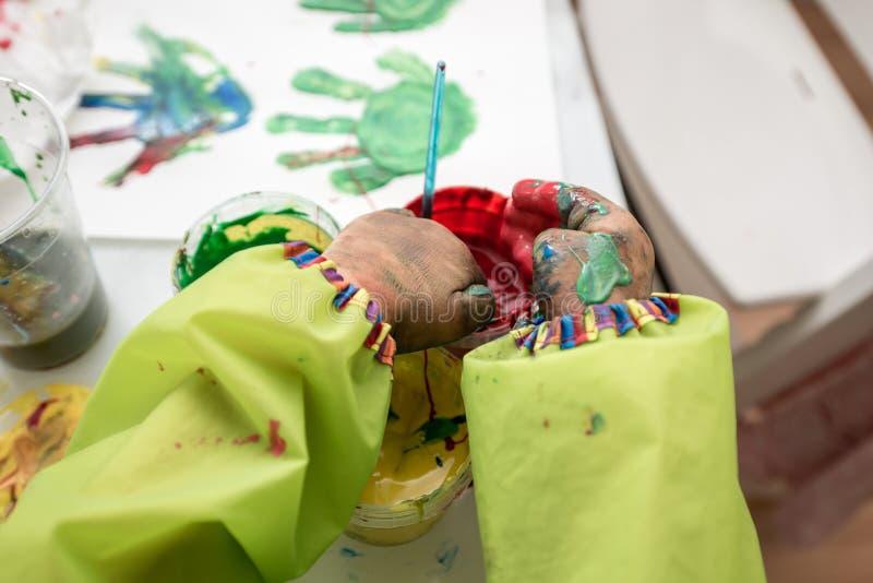 Petites mains écopant et mélangeant les peintures colorées de doigt photographie stock libre de droits