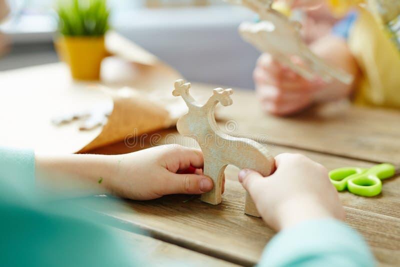 Petites mains tenant le jouet en bois images libres de droits