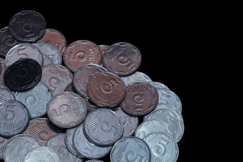 Petites pièces de monnaie ukrainiennes d'isolement sur le fond noir Plan rapproché photos stock
