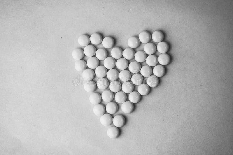 Petites pilules rondes pharmaceptic médicales, vitamines, drogues, antibiotiques sous forme de coeur sur un fond noir et blanc photo libre de droits