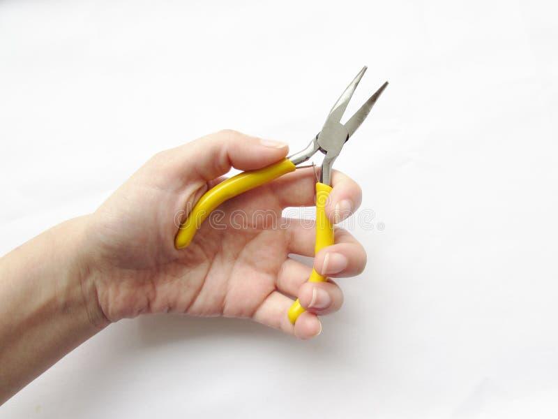 Petites pinces tordues avec les poignées jaunes lumineuses dans l'objet de main gauche sur un fond blanc photo stock
