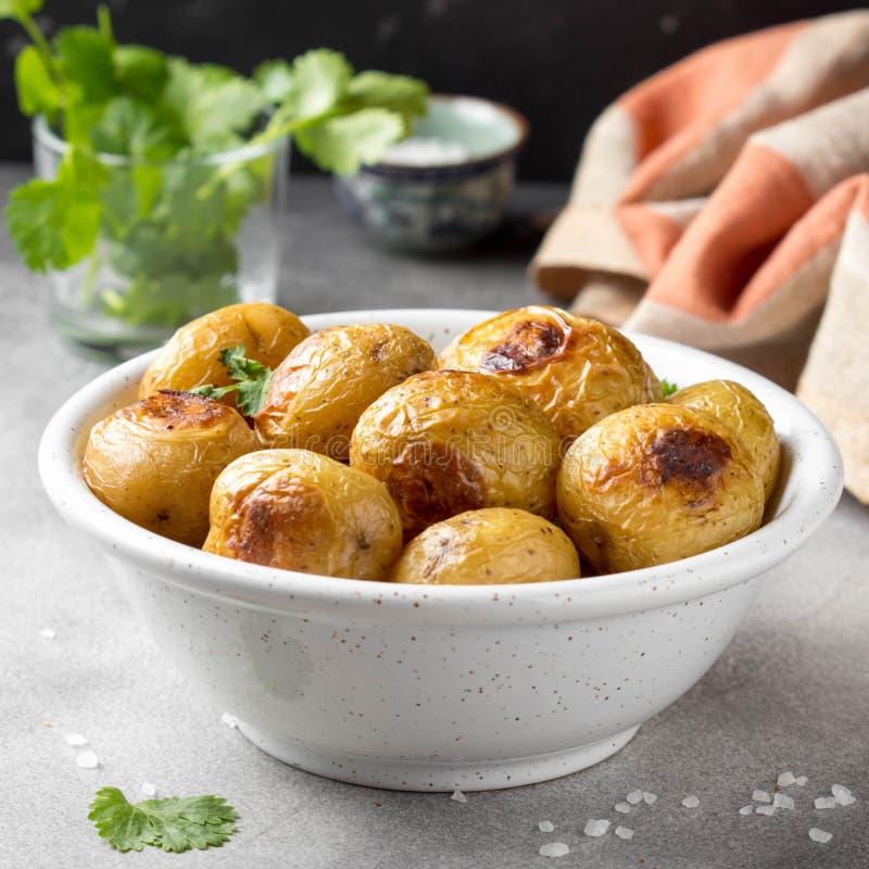 Petites pommes de terre entières (cuites au four) frites avec les herbes et le sel dans la cuvette, croûte vermeille, nourriture  image libre de droits