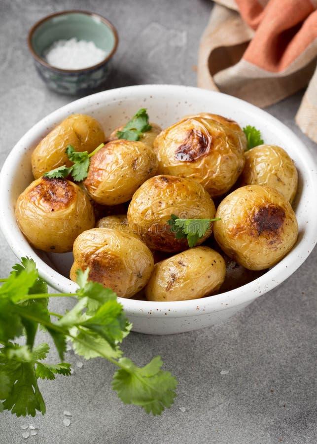 Petites pommes de terre enti?res (cuites au four) frites avec les herbes et le sel dans la cuvette, cro?te vermeille, nourriture  images libres de droits