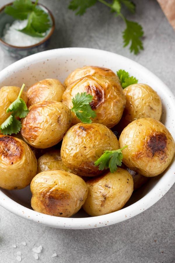 Petites pommes de terre enti?res (cuites au four) frites avec les herbes et le sel dans la cuvette, cro?te vermeille, nourriture  photographie stock libre de droits
