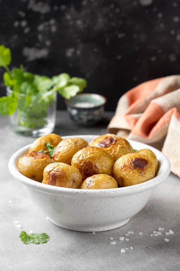 Petites pommes de terre enti?res (cuites au four) frites avec les herbes et le sel dans la cuvette, cro?te vermeille, nourriture  images stock