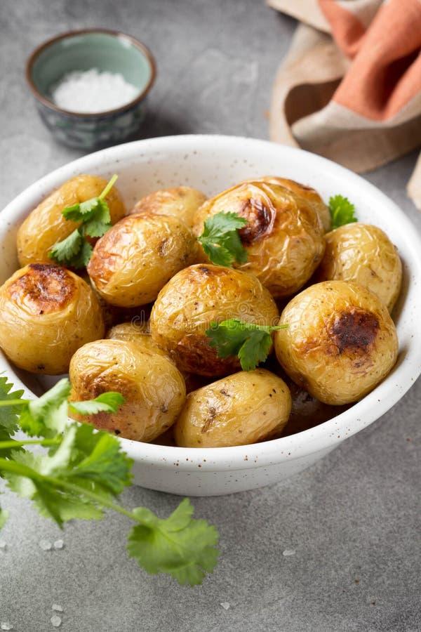 Petites pommes de terre enti?res (cuites au four) frites avec les herbes et le sel dans la cuvette, cro?te vermeille, nourriture  photo libre de droits