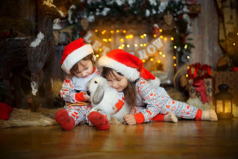 Petites soeurs dans des pyjamas au réveillon de Noël photos libres de droits