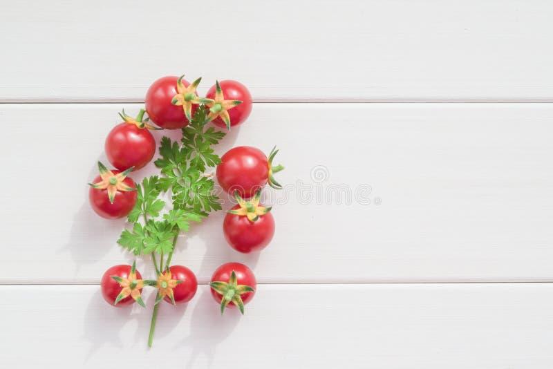 Petites tomates-cerises rouges fraîches avec un brin de persil vert sur une table en bois légère, images libres de droits