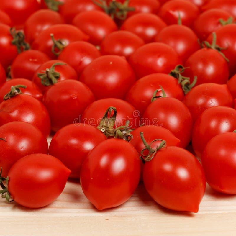 Petites tomates et herbes fraîches sur le fond en bois photographie stock libre de droits