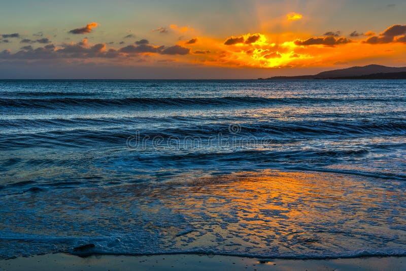 Petites vagues par le rivage à Alghero au coucher du soleil photographie stock libre de droits