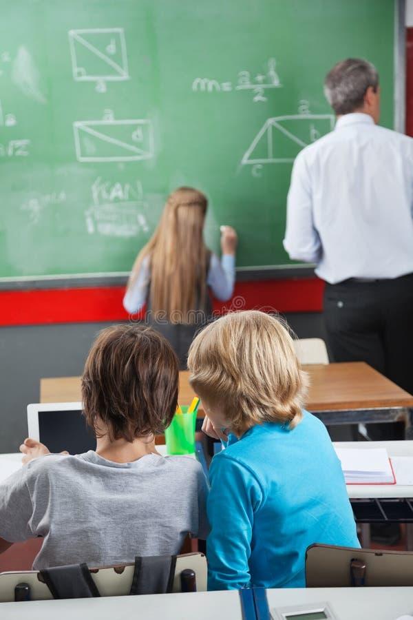 Petits écoliers à l'aide de la Tablette de Digital au bureau photo stock