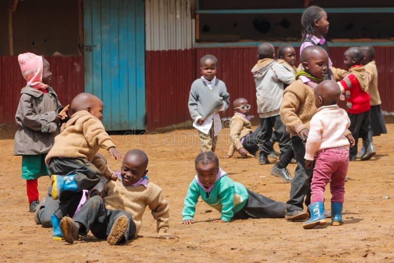 Petits écoliers africains sur un terrain de jeu photographie stock