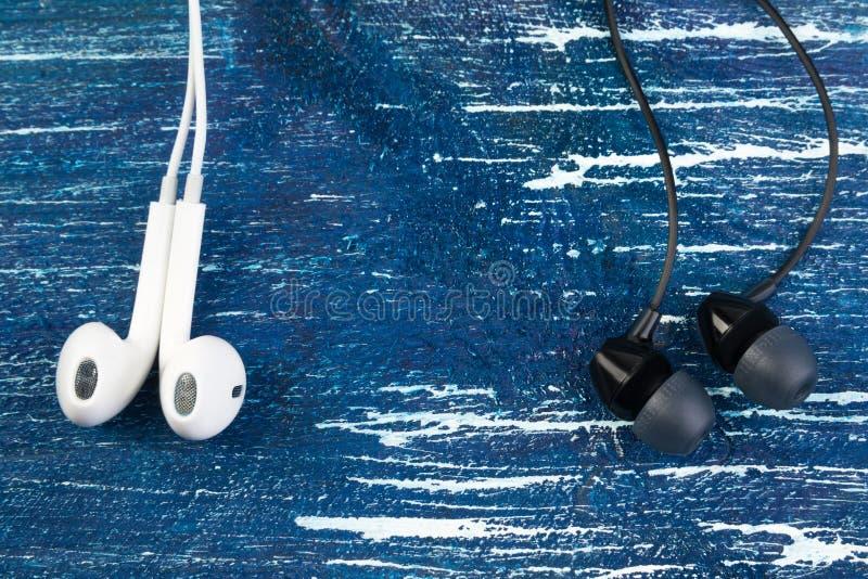 Petits écouteurs blancs et noirs sur le fond d'isolement en bois de blues-jean Cadre horizontal photo stock