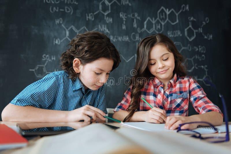 Petits élèves diligents appréciant la classe à l'école photos libres de droits