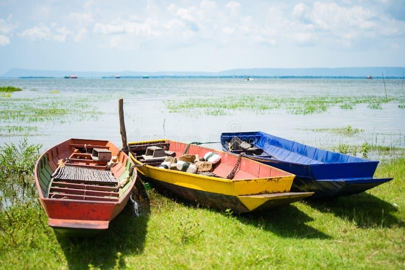 Petits bateaux de pêche colorés avec des pierres d'ancre à stabiliser et images stock
