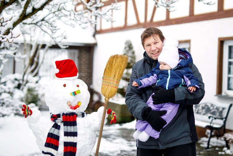 Petits beaux bébé et père mignons le jour d'hiver avec la neige et le bonhomme de neige Enfant de sourire heureux, fille adorable photographie stock libre de droits