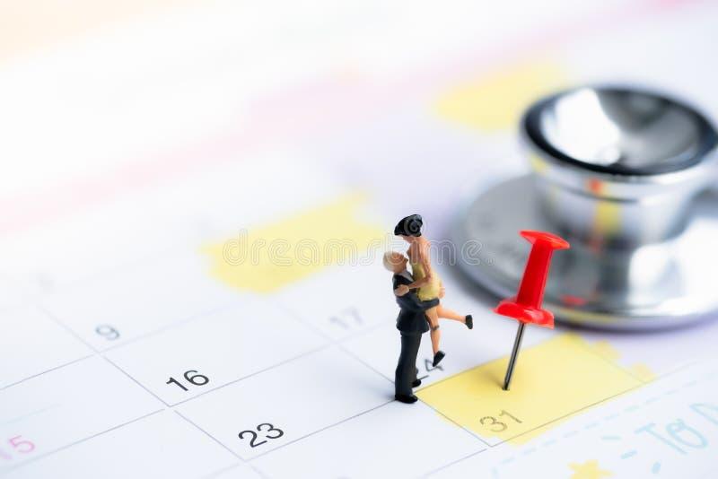 Petits chiffres de couples dans l'amour se tenant sur le fond de calendrier photo stock