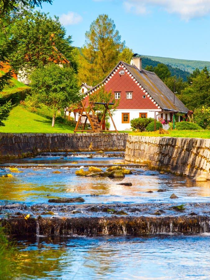 Petits cottage de montagne et terrain de jeu rustiques de jardin au petit courant Paysage rural le jour ensoleillé photo libre de droits