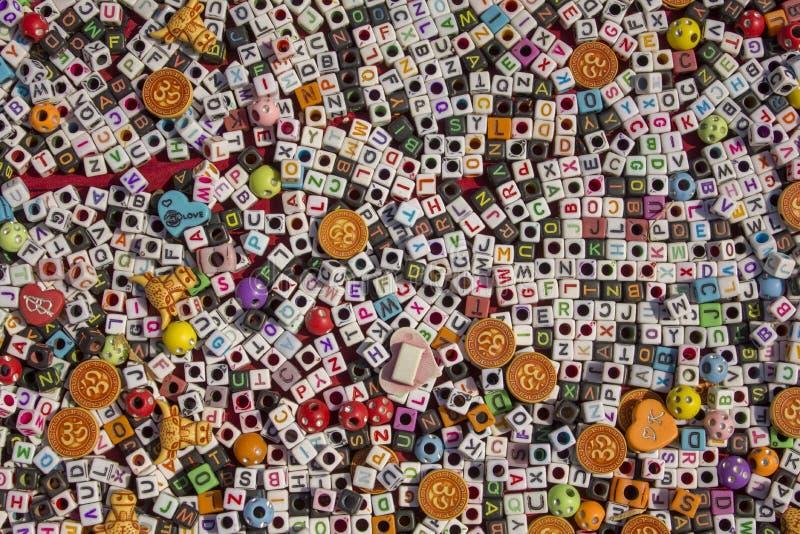 Petits cubes blancs et noirs avec des trous et le mensonge d'alphabet anglais sur la surface rouge du plan rapproché de table, le image libre de droits