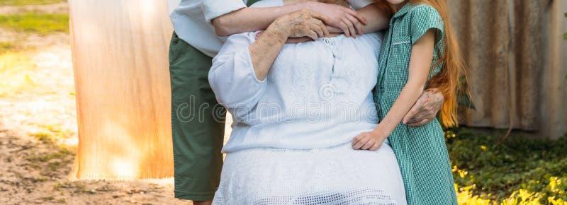 Petits-enfants, enfants étreignant la grand-mère, femme agée grand-mère et petits-enfants de réunion la grand-mère embrasse l'pet photographie stock