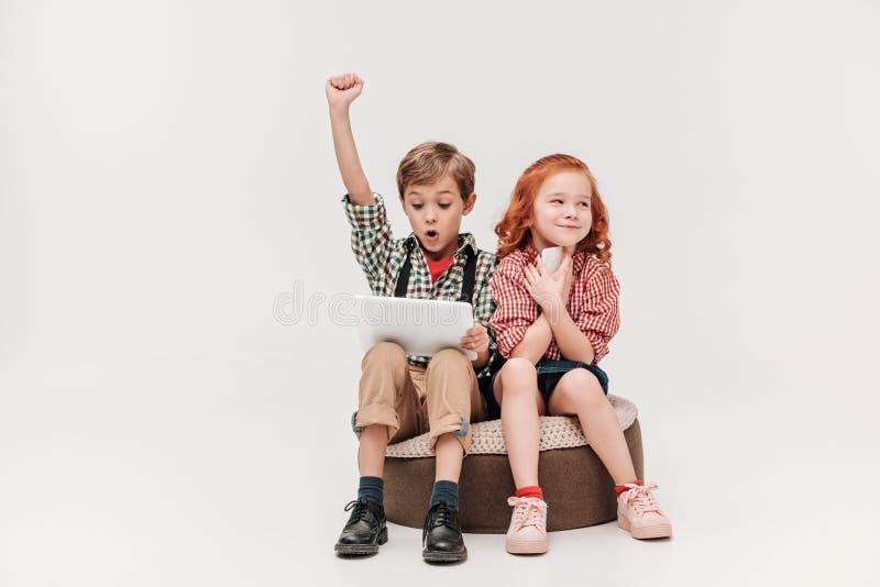 petits enfants adorables à l'aide des dispositifs numériques images libres de droits