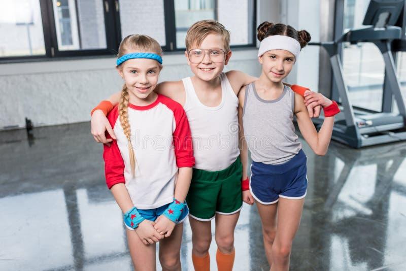 Petits enfants adorables dans les vêtements de sport se tenant embrassants et souriants à l'appareil-photo dans le gymnase image stock