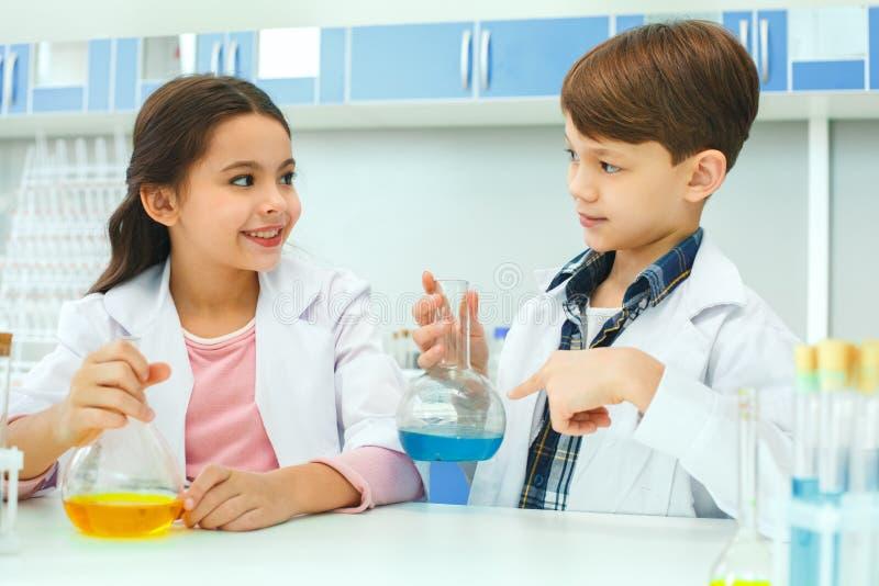 Petits enfants apprenant la chimie en ingrédients d'expérience de laboratoire d'école photo libre de droits