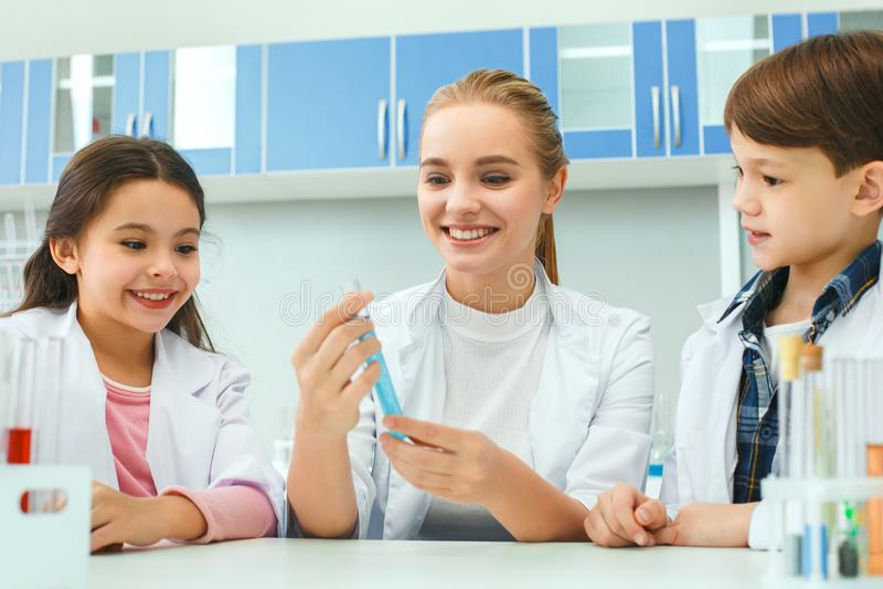 Petits enfants avec le professeur dans la leçon de liquide de laboratoire d'école images libres de droits
