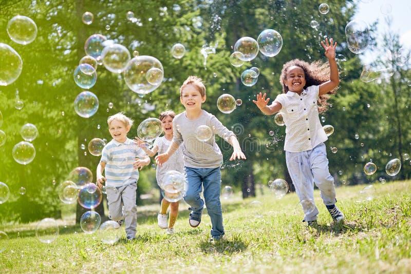 Petits enfants ayant l'amusement dehors image stock