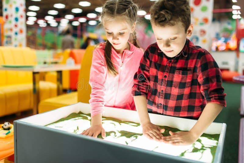 Petits enfants ayant l'amusement sur des attractions photo libre de droits