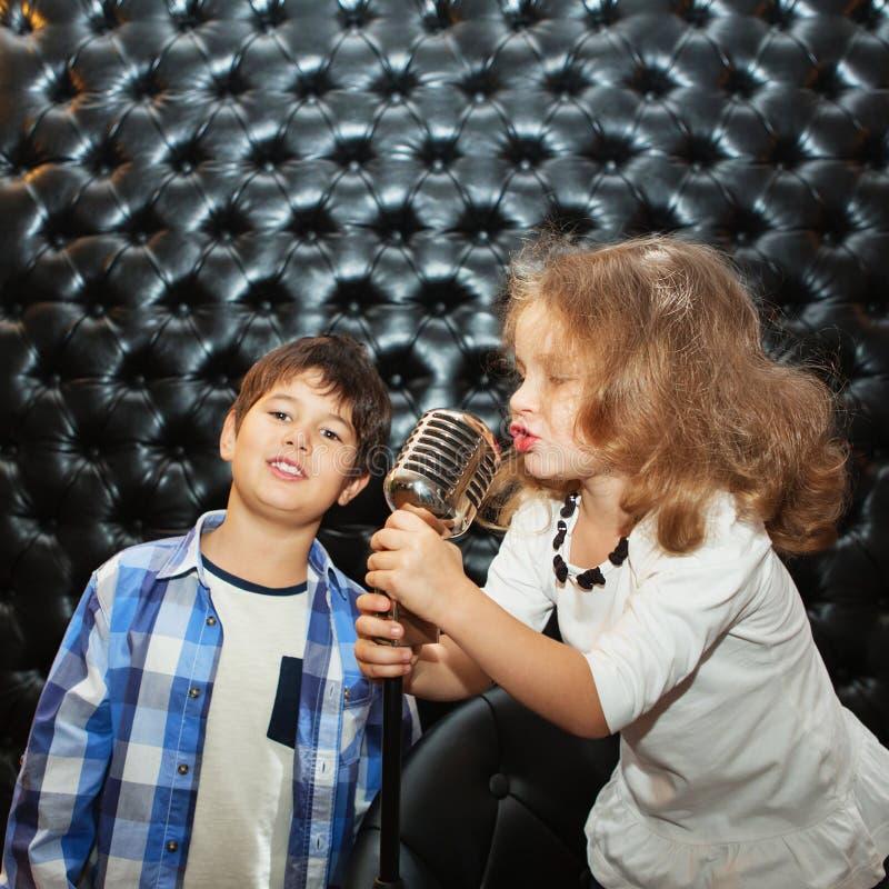 Petits enfants chanteurs avec un microphone sur un support photos stock