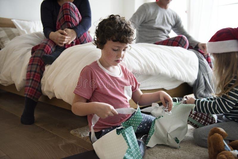 Petits enfants déroulant des cadeaux de Noël photos stock