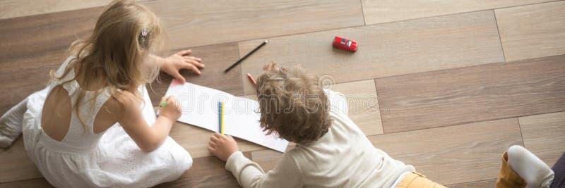Petits enfants de vue ci-dessus horizontale dessinant sur le plancher en bois chaud photo libre de droits