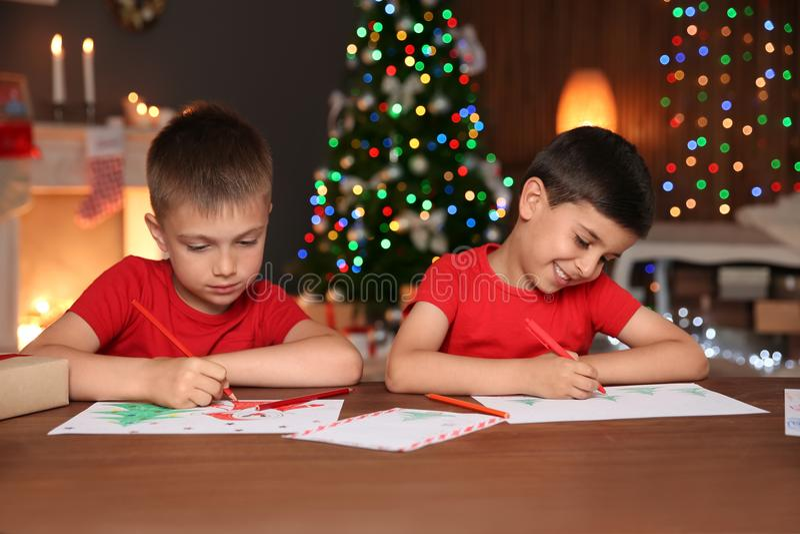 Petits enfants dessinant des photos à la maison photo stock