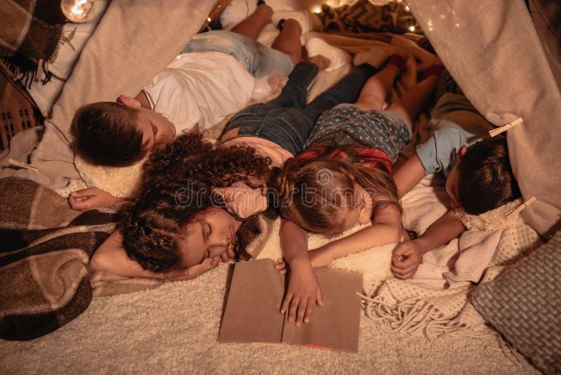 Petits enfants dormant après livre de lecture à la maison photo stock