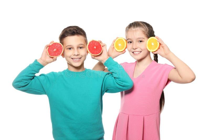 Petits enfants drôles avec des agrumes sur le fond blanc images libres de droits