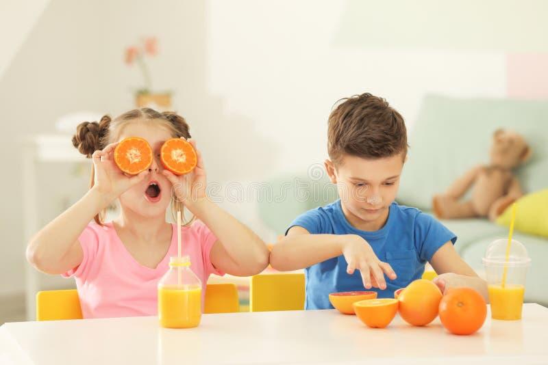 Petits enfants drôles avec les agrumes et le jus à la maison images stock