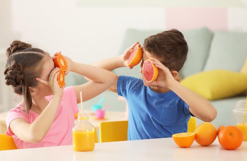 Petits enfants drôles avec les agrumes et le jus à la maison photo stock
