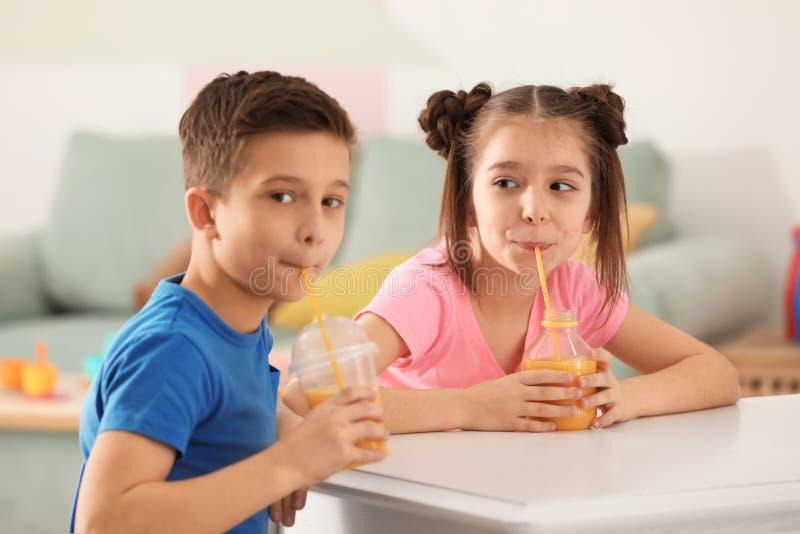 Petits enfants drôles buvant du jus d'agrumes à la maison photos stock