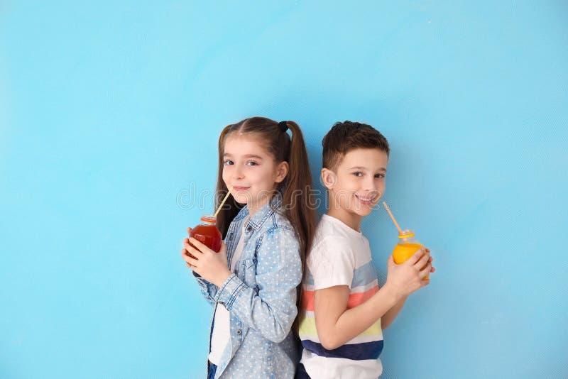 Petits enfants drôles buvant du jus d'agrumes sur le fond de couleur photos stock